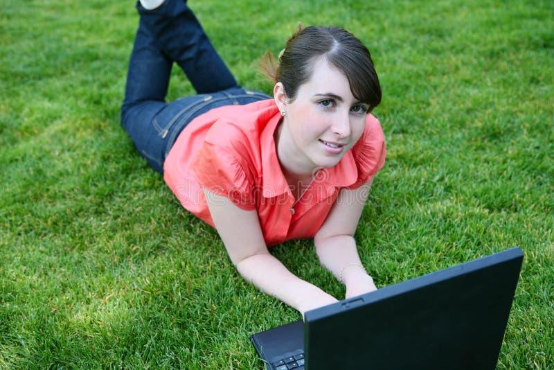 Mädchen auf Laptop-Computer lizenzfreie stockfotografie