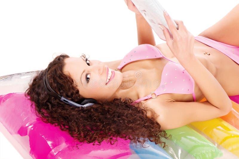 Mädchen auf Luftmatraze-Lesezeitung lizenzfreie stockfotos