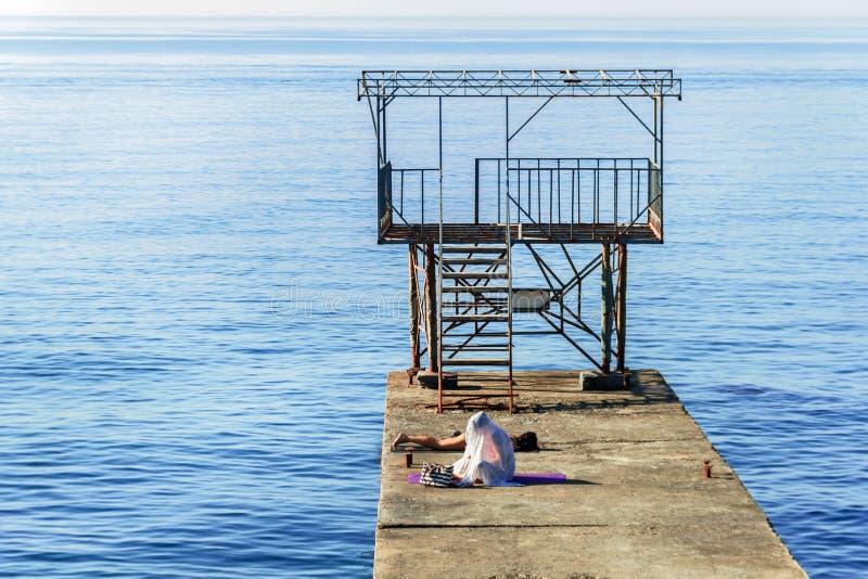 Mädchen auf Pier durch Meer stockbild