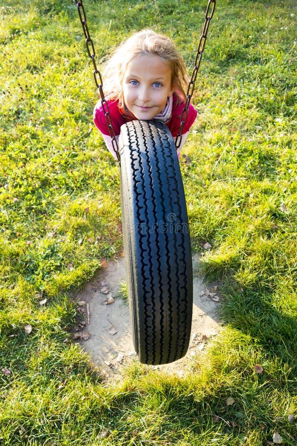 Mädchen auf Reifenschwingen lizenzfreies stockbild