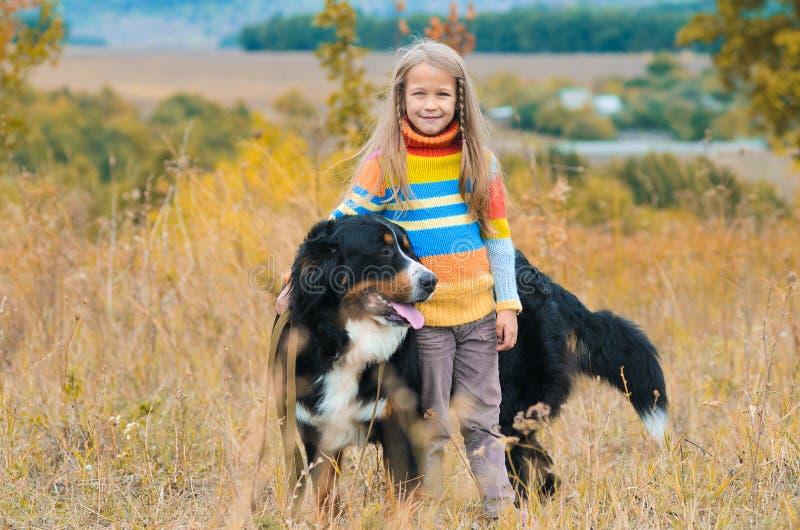Mädchen auf Weg mit ihrem Hundefreund auf Herbsthügeln stockfotos