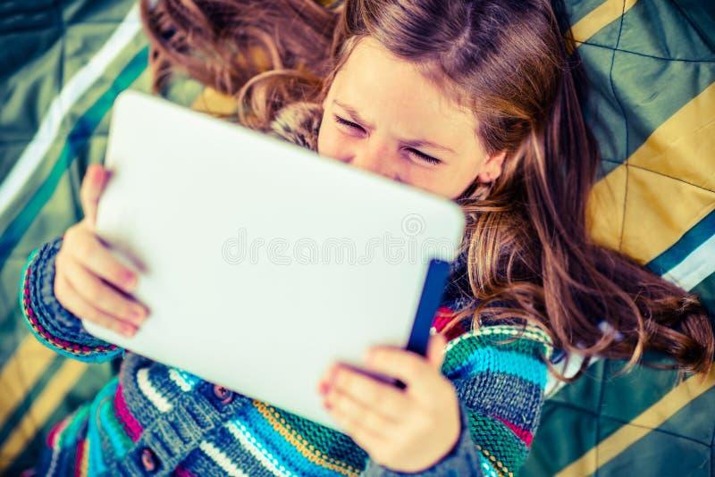 Mädchen-aufpassender Film auf Tablet lizenzfreie stockfotografie