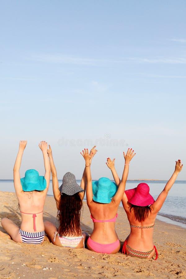 Mädchen in Badeanzügen sitzen zurück auf dem Strand stockbild