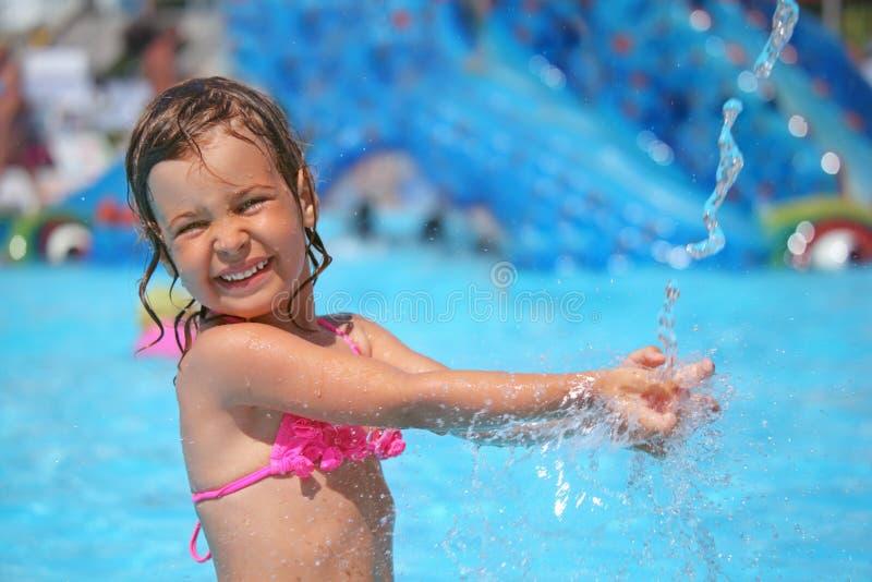 Mädchen badet im Pool unter Wasser spritzt lizenzfreies stockfoto