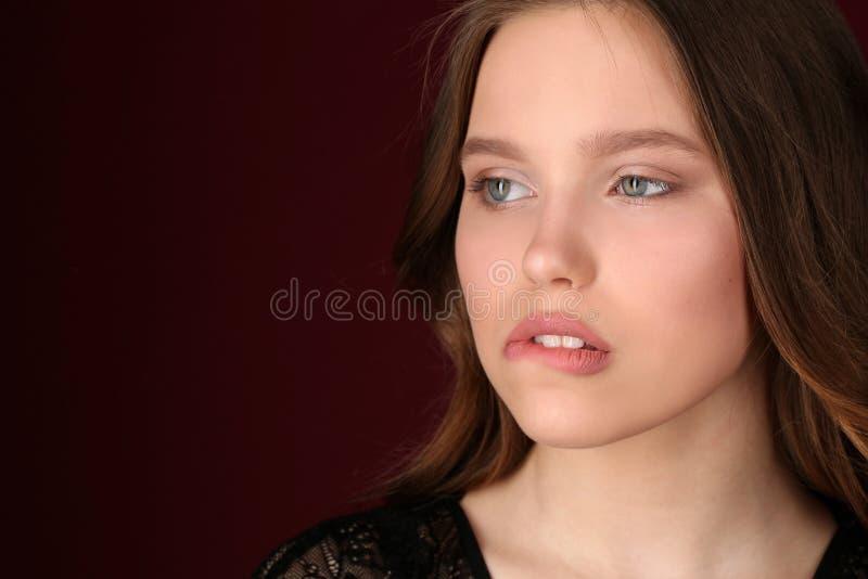 Mädchen beißt ihre Lippe Abschluss oben Dunkelroter Hintergrund stockbild