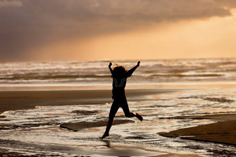 Mädchen bei Sonnenuntergang springt in Wasser stockfotos