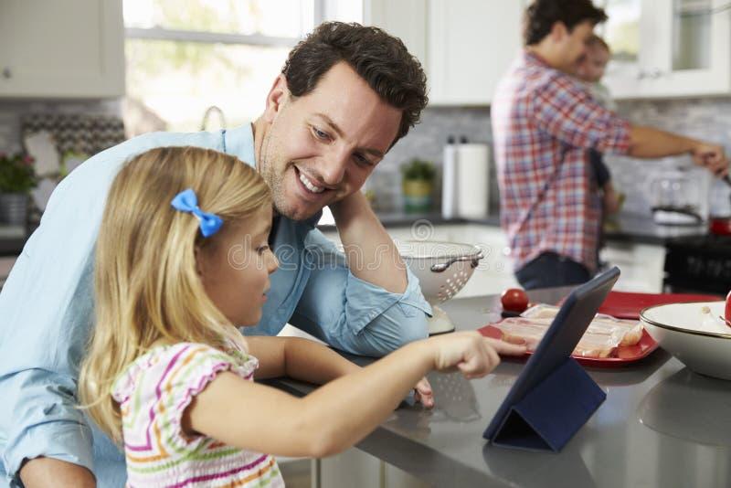 Mädchen benutzt Tablette in der Küche mit Vati, während anderer Vati kocht lizenzfreie stockbilder