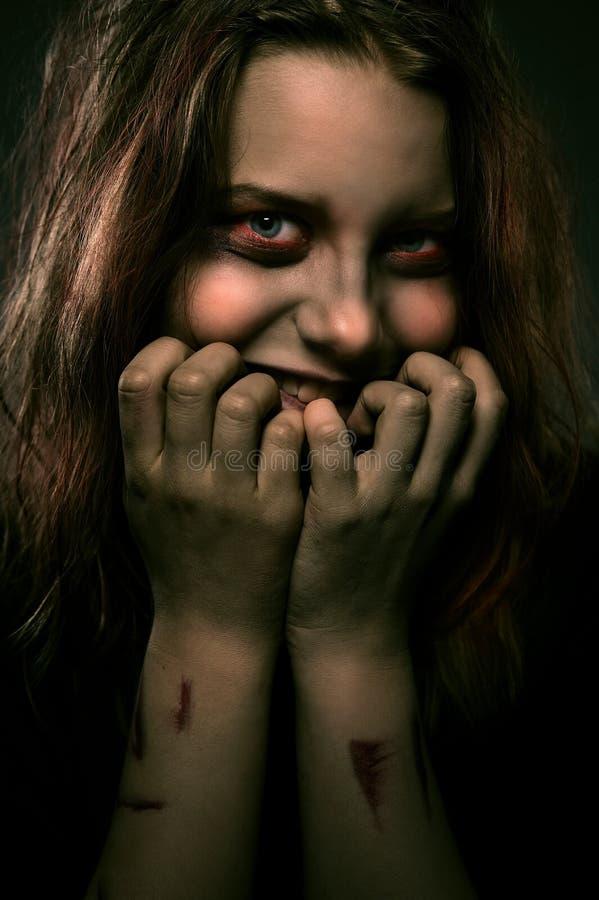 Mädchen besessen von einem Dämon mit einem unheimlichen Lächeln lizenzfreie stockfotos
