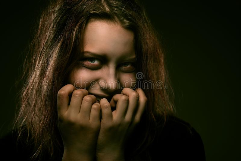 Mädchen besessen von einem Dämon mit einem unheimlichen Lächeln lizenzfreies stockfoto