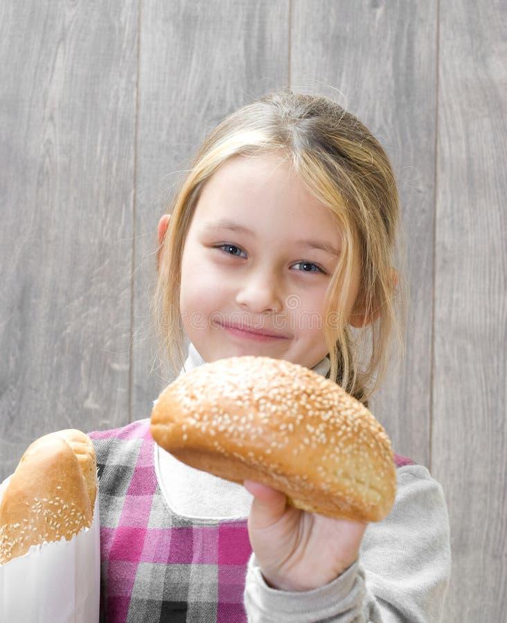 Mädchen bietet geschmackvolles Brötchen an stockfotos