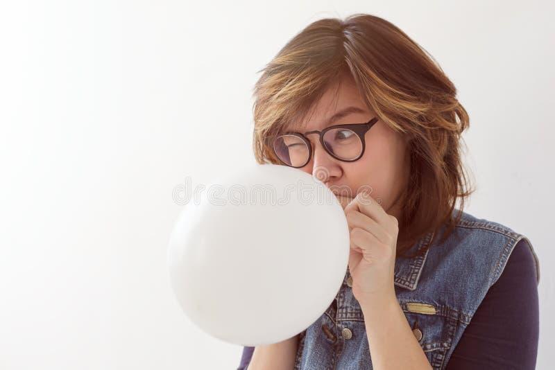 Mädchen bläst einen Ballon auf, der zu einer Partei fertig wird lizenzfreies stockbild