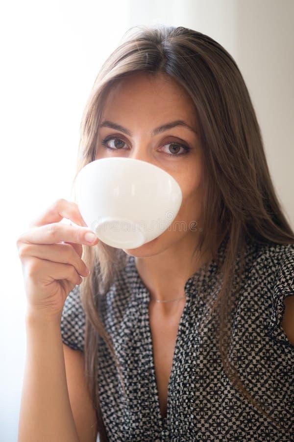 Mädchen blickt flüchtig, während sie Kaffee trinkt stockfoto
