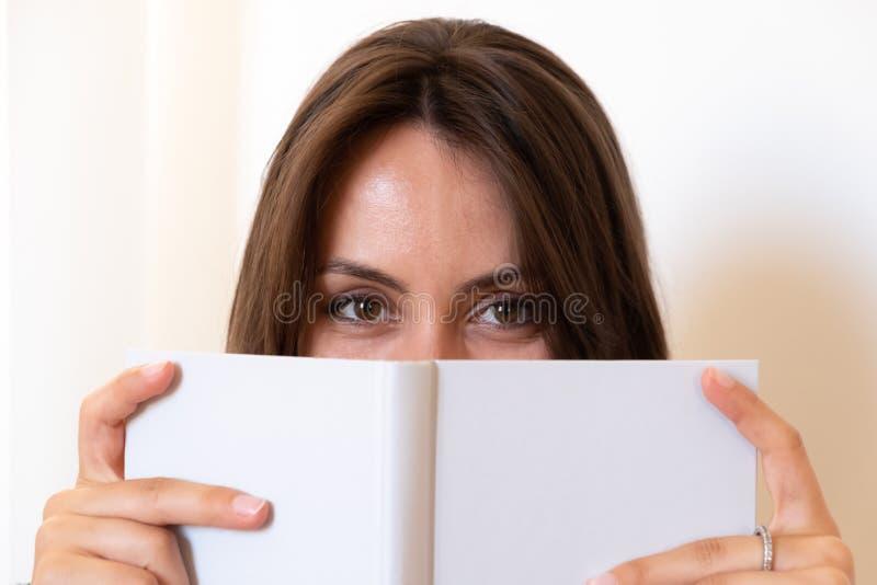Mädchen blickt hinter einem Buch flüchtig lizenzfreie stockfotografie