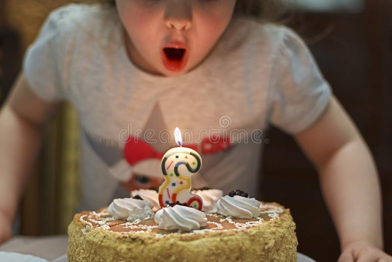 Mädchen brennt heraus eine Kerze auf einem Geburtstagskuchen durch stockfotografie