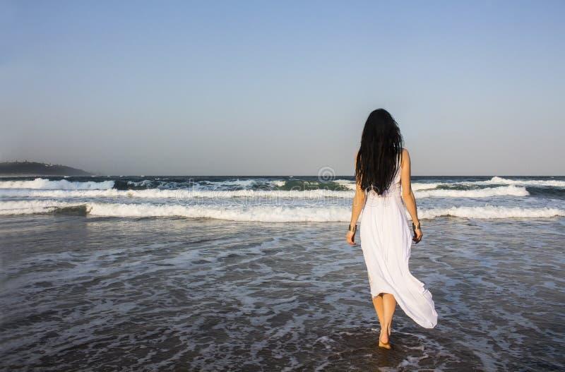 Mädchen Brunette im weißen Kleid, das den Indischen Ozean kommt lizenzfreie stockfotos