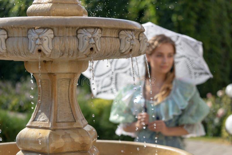 Mädchen am Brunnen mit weißem Regenschirm stockbild