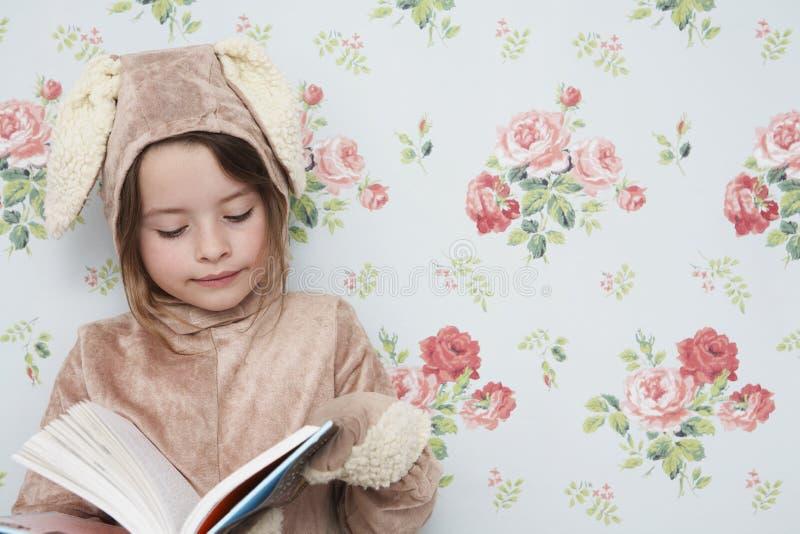 Mädchen in Bunny Costume Reading Against Wallpaper lizenzfreies stockfoto