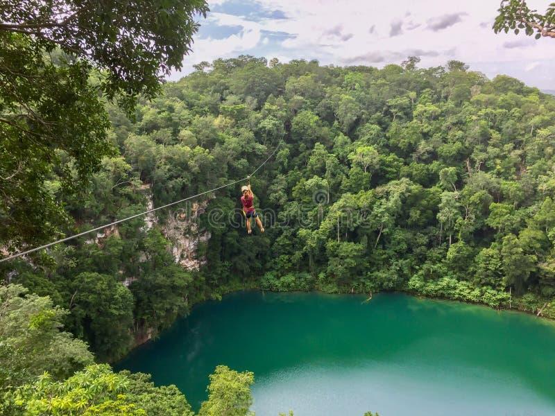 Mädchen, das über dem Wasser eines cenote im mexikanischen Dschungel ziplining ist lizenzfreie stockbilder