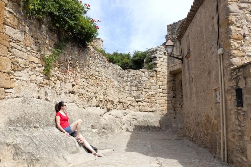 Mädchen, das über einer Wand in einer Straße eines Dorfs stillsteht stockfotos