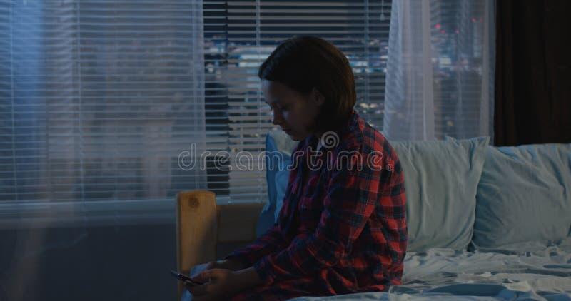 Mädchen, das allein in ihrem Schlafzimmer sitzt stockbild