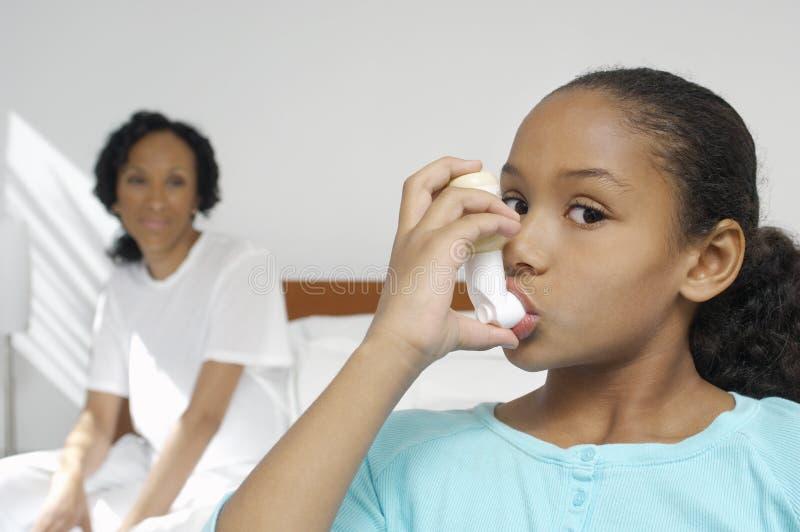 Mädchen, das Asthma-Inhalator verwendet stockfotos