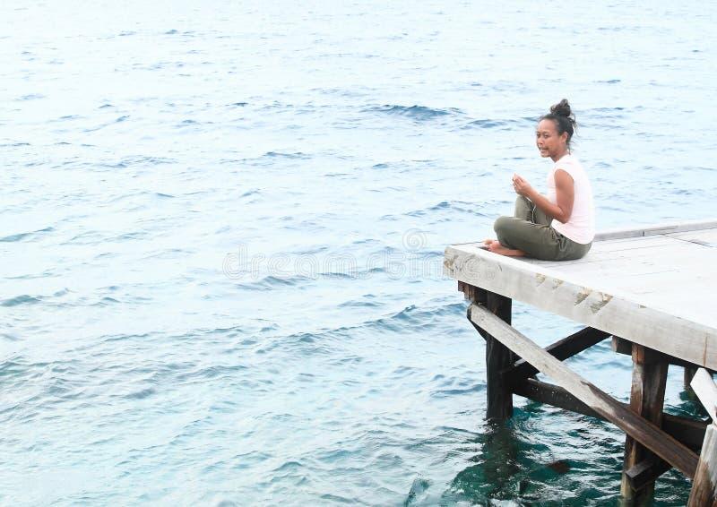 Mädchen, das auf Anlegestelle durch Meer sitzt lizenzfreie stockbilder