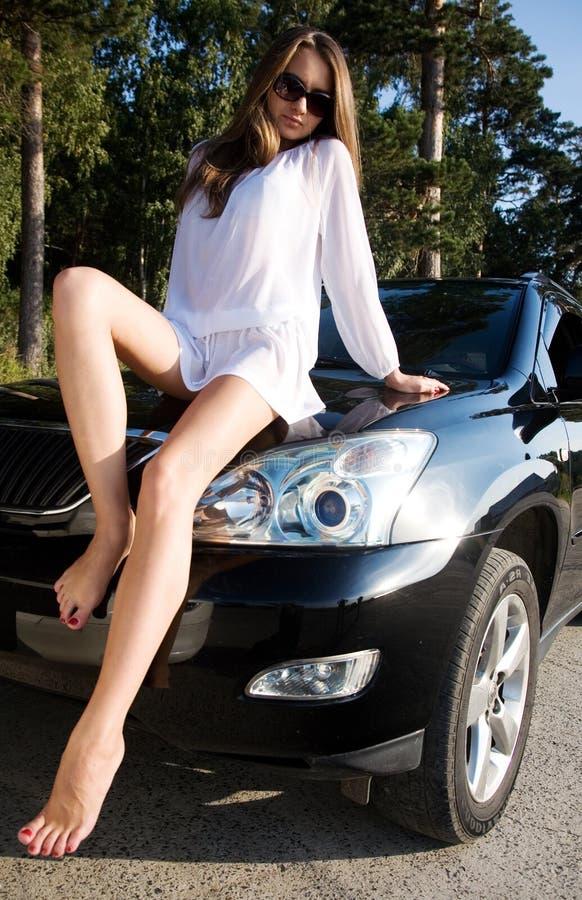 Mädchen, das auf Auto sitzt stockbild