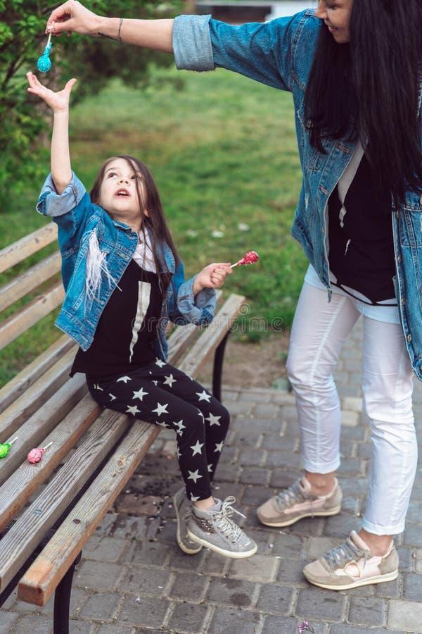 Mädchen, das auf Bank mit Süßigkeiten sitzt lizenzfreies stockbild