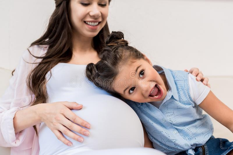 Mädchen, das auf Bauch der schwangeren Mutter hört lizenzfreie stockbilder