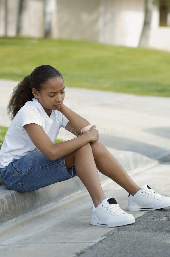 Mädchen, das auf Beschränkung sitzt stockfotografie