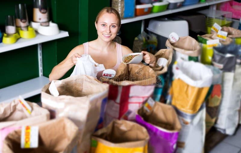 Mädchen, das auf bester Nahrung für Haustiere entscheidet lizenzfreie stockfotografie