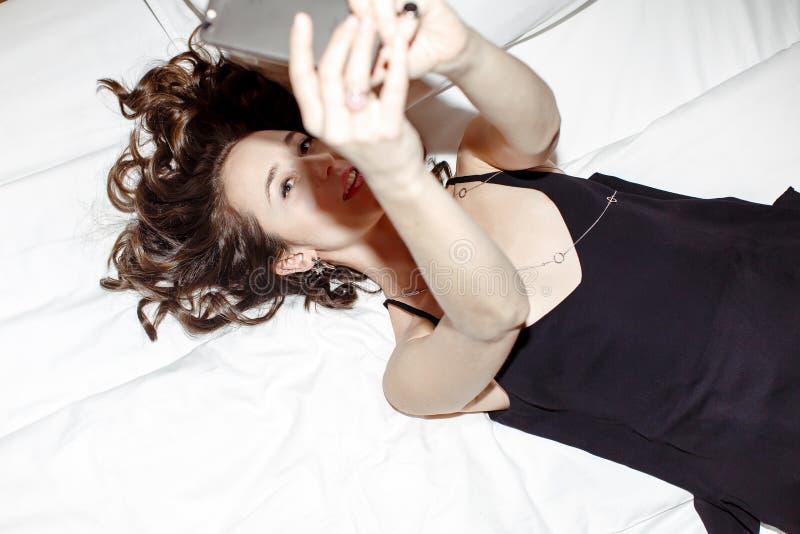 Mädchen, das auf Bett legt und selfie an ihrem Telefon macht lizenzfreies stockbild