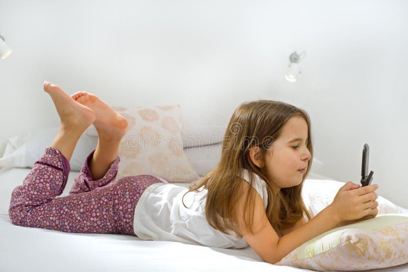 Mädchen, das auf Bett mit Handy liegt lizenzfreies stockfoto