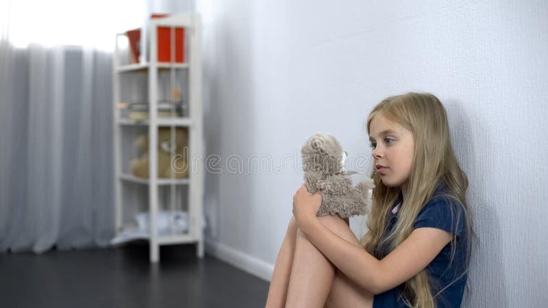 Mädchen, das auf Boden sitzt und mit Teddybären, bester Spielzeugfreund, Annahmeprogramm spielt stockbilder