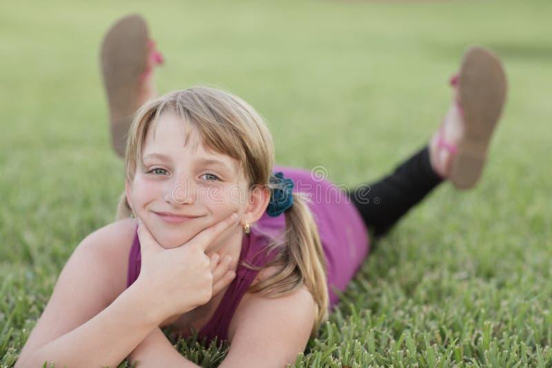 Mädchen, das auf das Gras legt stockbilder