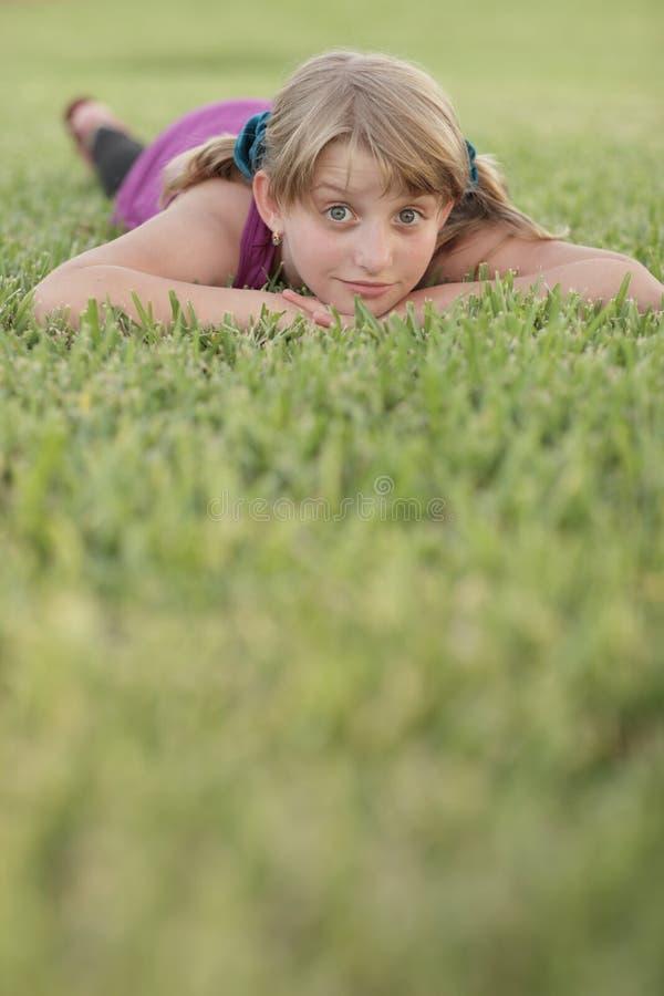 Mädchen, das auf das Gras legt lizenzfreie stockfotografie