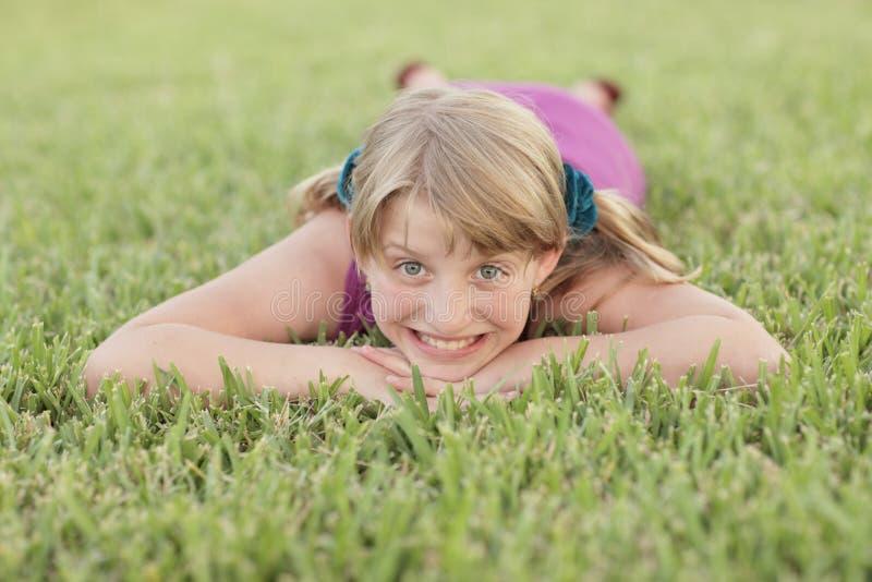 Mädchen, das auf das Gras legt lizenzfreie stockbilder