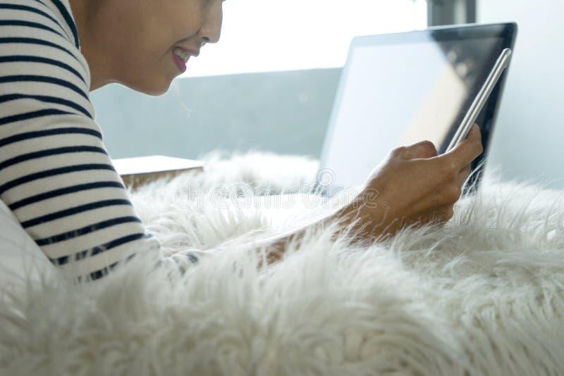 Mädchen, das auf dem Bett liegt, ihren Smartphone zu spielen lizenzfreies stockfoto