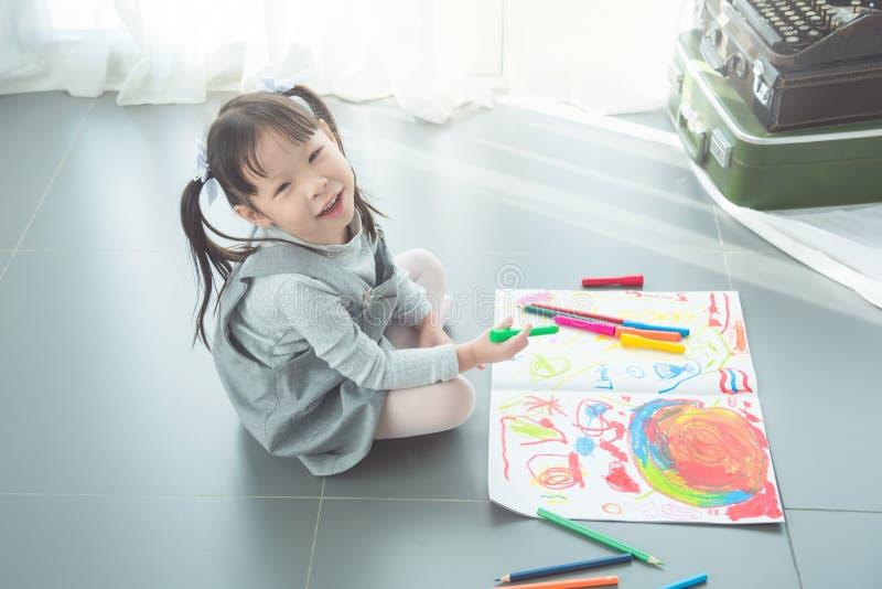 Mädchen, das auf dem Boden und dem zeichnenden Bild durch Zeichenstift sitzt stockfotografie