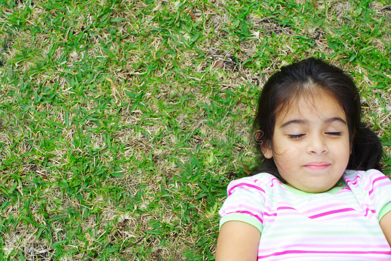 Mädchen, das auf dem Gras liegt lizenzfreie stockfotos
