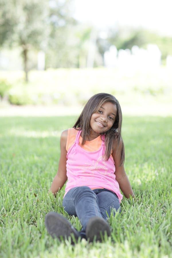 Mädchen, das auf dem Gras sitzt stockbild