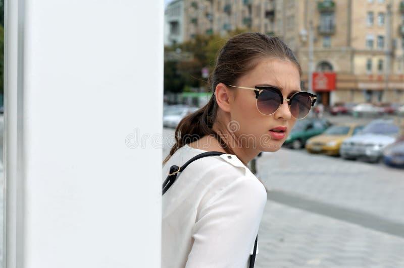 Mädchen, das auf dem Hintergrund der Stadt aufwirft stockfotos