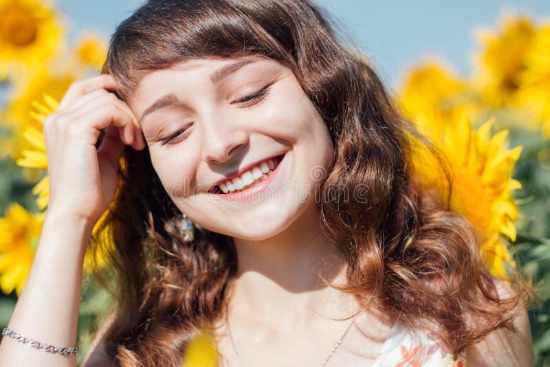 Mädchen, das auf dem Hintergrund des Sonnenblumenfelds lacht lizenzfreies stockfoto