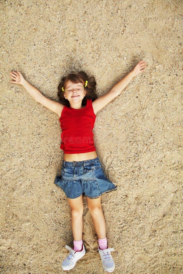 Mädchen, das auf dem Sand liegt stockfotos