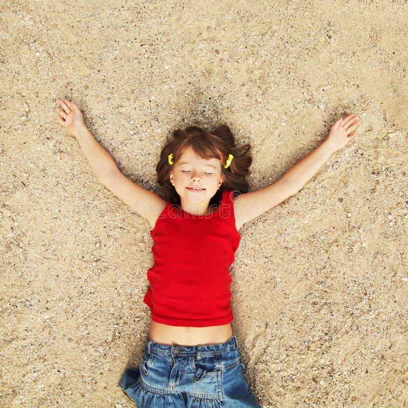 Mädchen, das auf dem Sand liegt lizenzfreie stockfotos