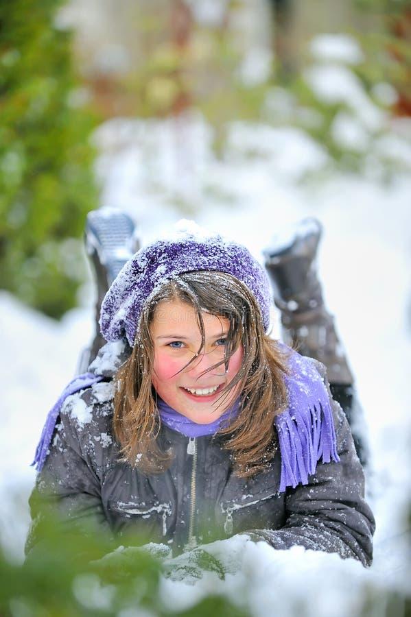 Mädchen, das auf dem Schnee niederlegt lizenzfreie stockfotografie