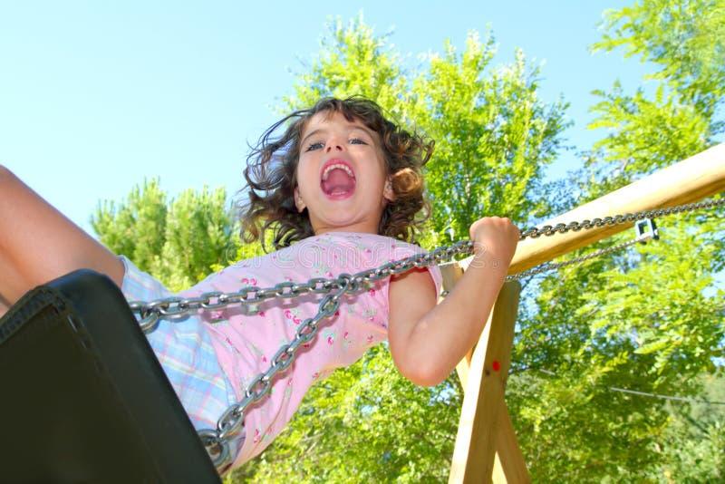 Mädchen, das auf dem Schwingen glücklich in den Bäumen im Freien schwingt stockfoto