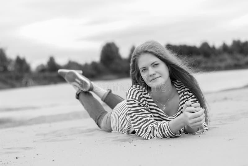 Mädchen, das auf dem Strand, auf den Banken des Flusses stillsteht Einfarbiges Bild stockbild