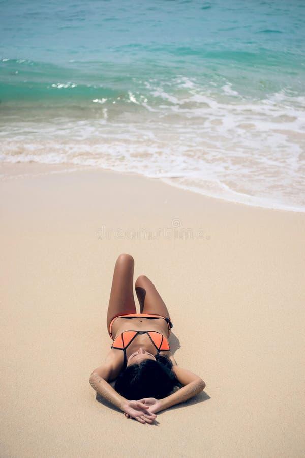 Mädchen, das auf dem Strand ein Sonnenbad nimmt stockfotografie