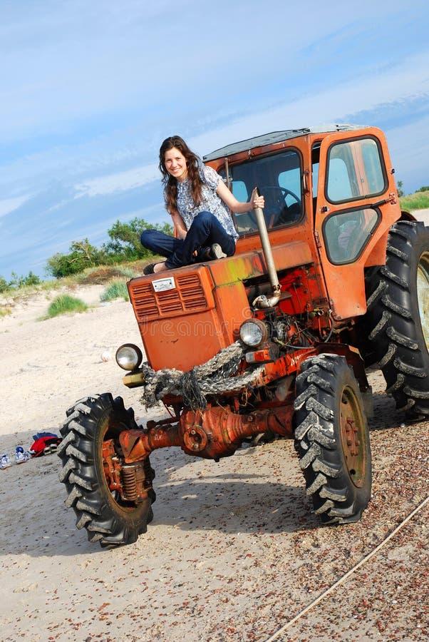 Mädchen, das auf dem Traktor sitzt lizenzfreie stockfotografie